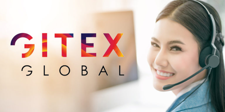 Asian woman with headset and in front of computer smiling over her shoulder at camera with GITEX Global logo beside her